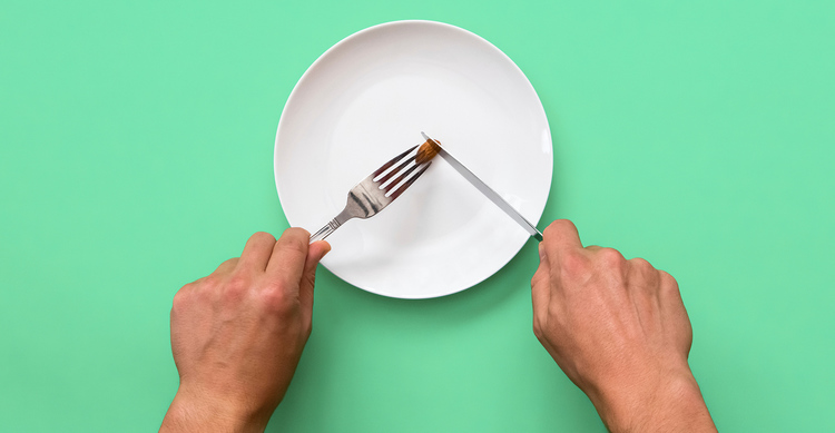 image of an almost being cut by a knife and fork on a plate on a sea foam green background