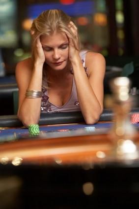 Blonde lady sitting at a poker table looking upset