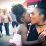 Mother kissing daughter on street